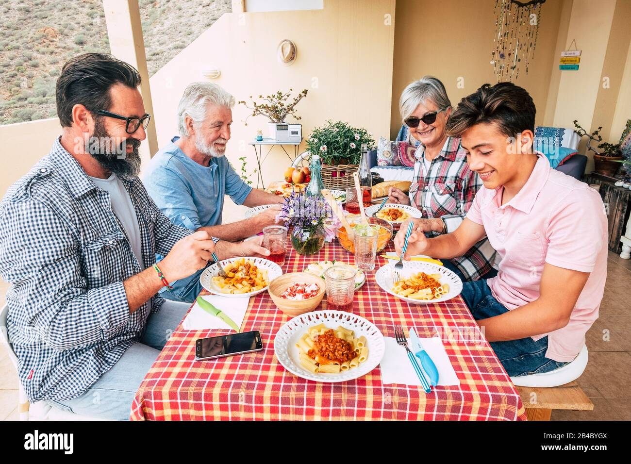 Family People Outdoor Lunch Together On A Red Table Mixed Ages Generations Enjoy And Have Fun With Italian Pasta On The Terrace At Home Father Grandfather And Son Stock Photo Alamy