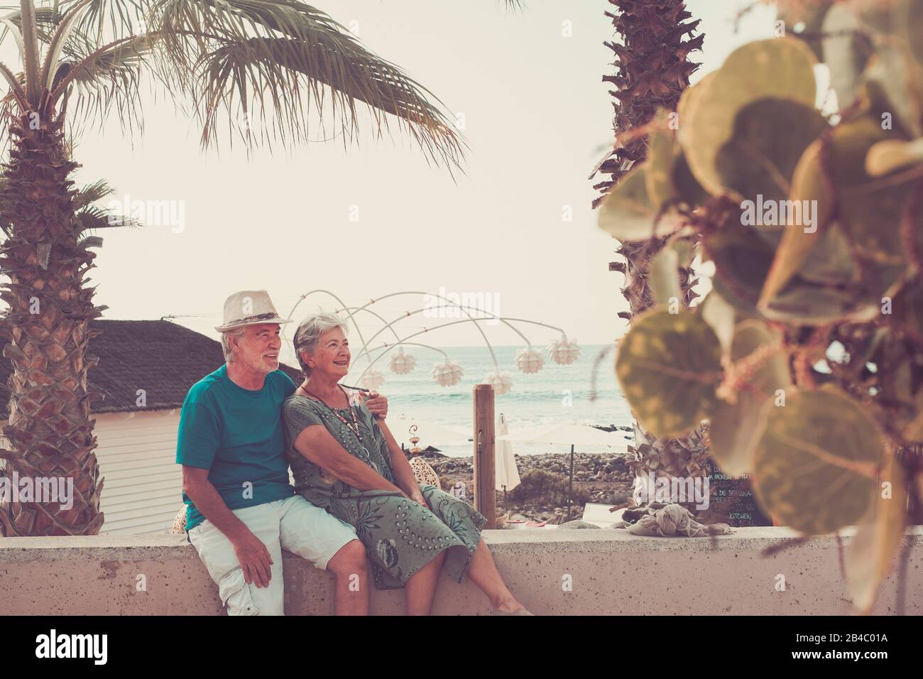 Happy senior adult caucasian people couple sitting and enojying outdoor leisure activity together hugged - forever life concept - vacation sea in background Stock Photo