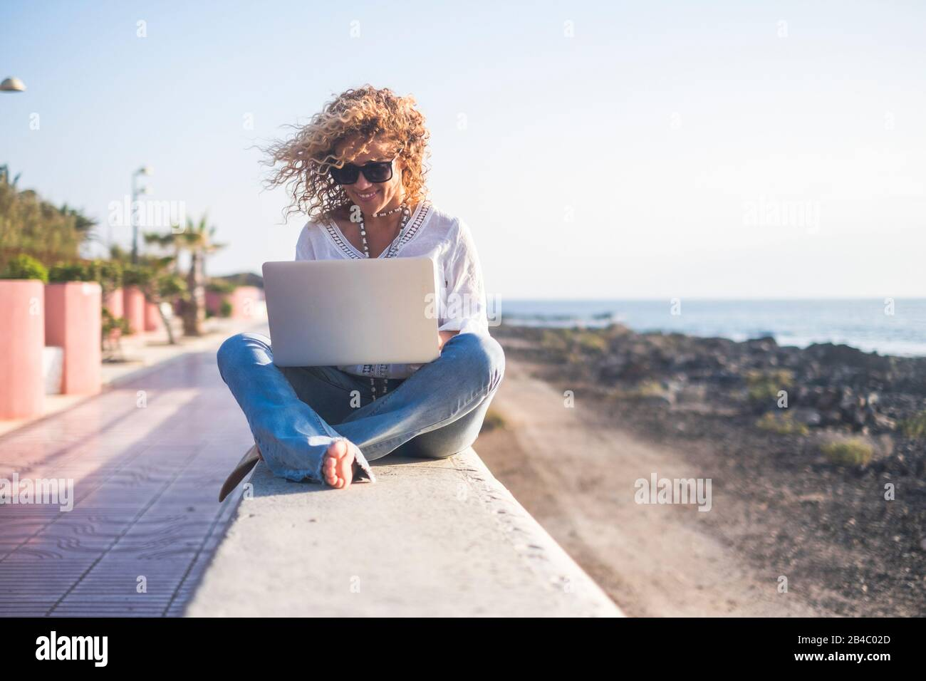 Cheerful beautiful blonde curly people young adult woman sitting outdoor with sea and sky in background working with tablet computer internet connected - freedom from office concept Stock Photo