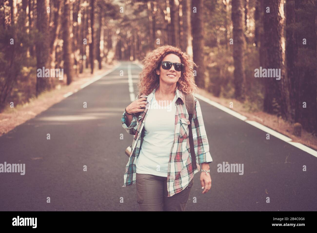 Cheerful happy free woman traveler people walking in the middle of a long road with forest and trees around - scenic travel concept - beautiful caucasian curly female enjoying the outdoor leisure activity Stock Photo