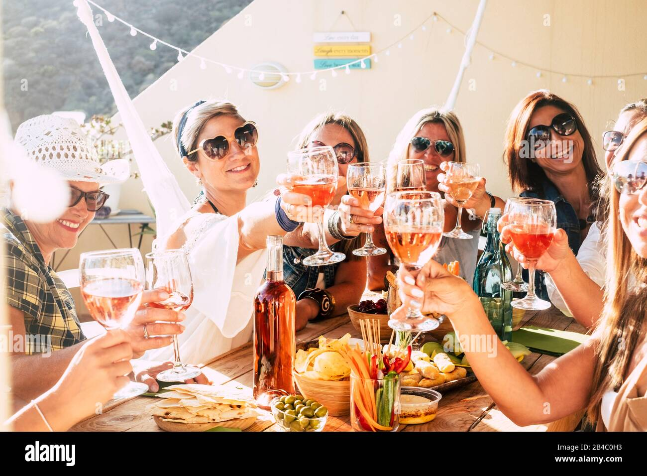 Cheerful group of happy female people clinking and toasting together with friendship and happiness - young and adult women have fun eating - food and beverage celebration concept Stock Photo