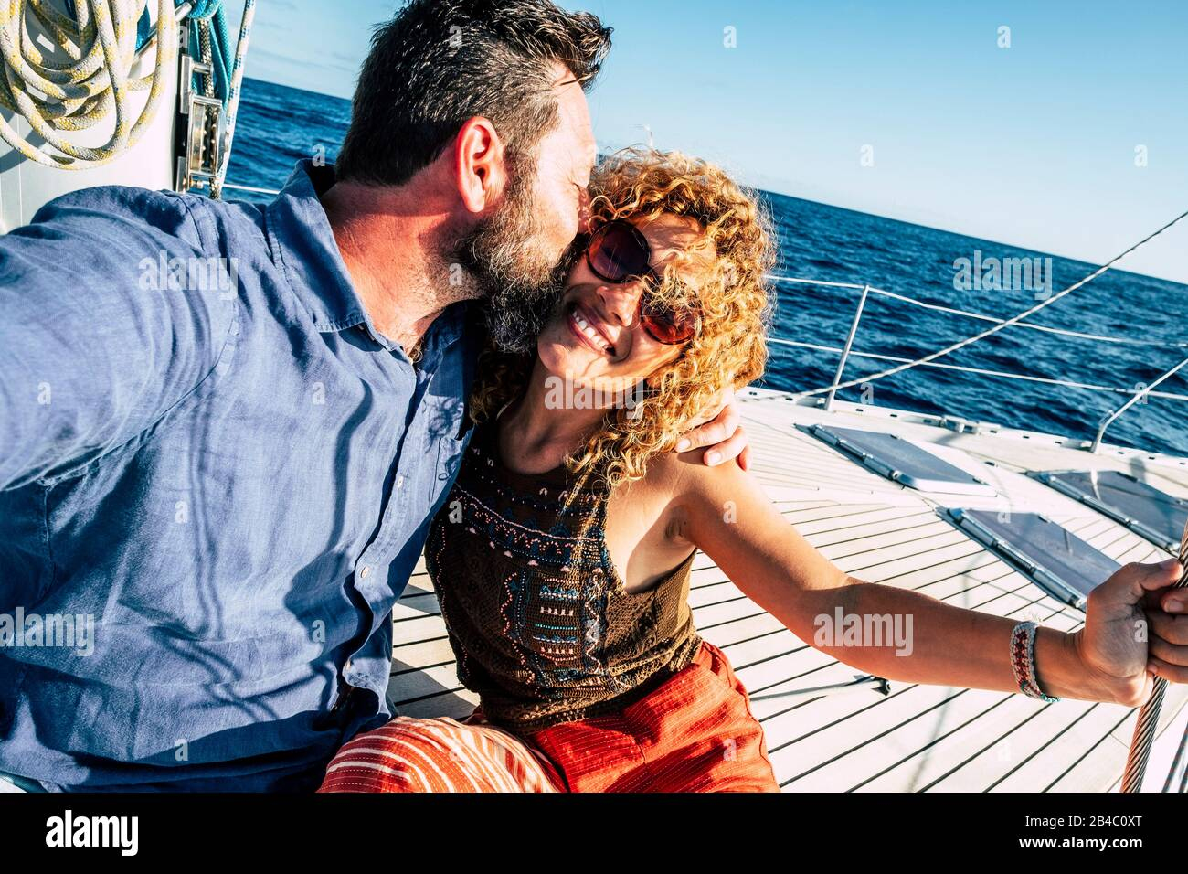 Happy tourist couple of traveler people in love enjoying the sail boat trip together having fun and smiling - cheerful adult man and woman under the summer sun in holiday vacation at the sea Stock Photo