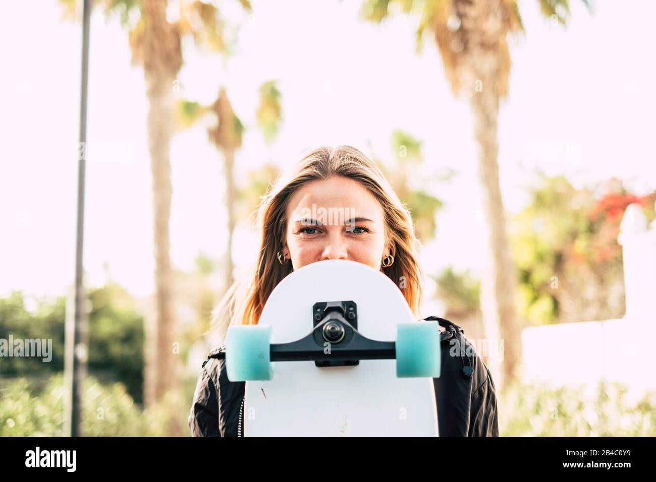 Modern cheerful beautiful blonde girl portrait with skateboard covering part of the pretty face - young millennial people outdoor concept enjoying lifestyle and sunny days Stock Photo