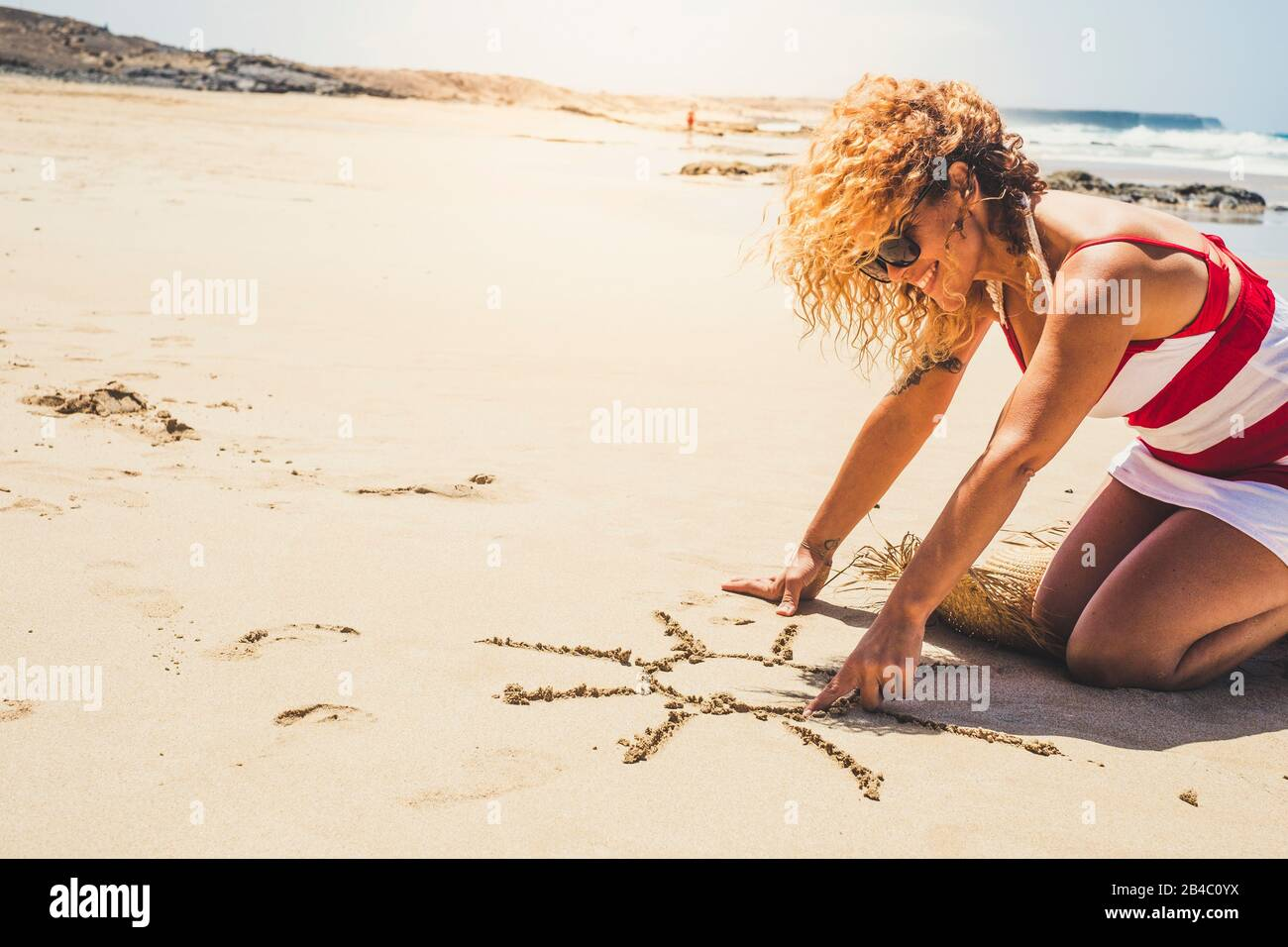 Happy cheerful woman on summer vacation enjoying the beach and the outdoor designing a sun on the sand - beautiful curly caucasian people lady in outdoor leisure activity Stock Photo