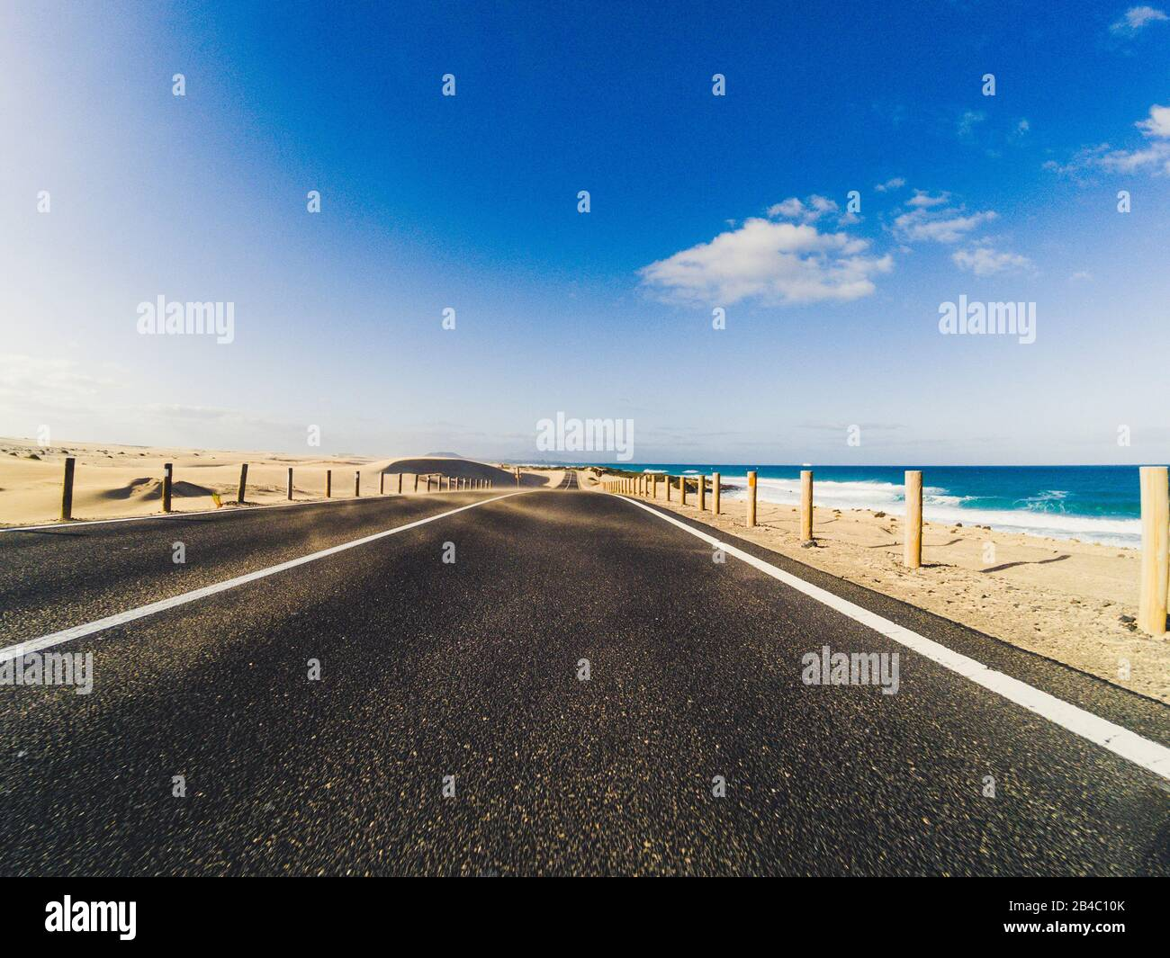 Long way road for travel car transportation concept with desert and beach on the side - sea water and blue clear beautiful sky in background - motion effect Stock Photo