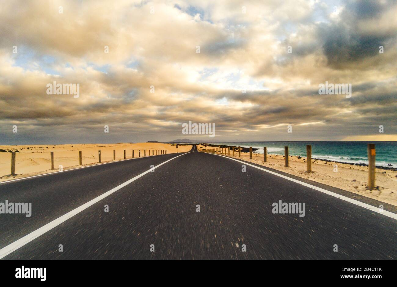 Long way road for travel car transportation concept with desert and beach on the side - sea water and cloudy beautiful sky in background - motion effect Stock Photo