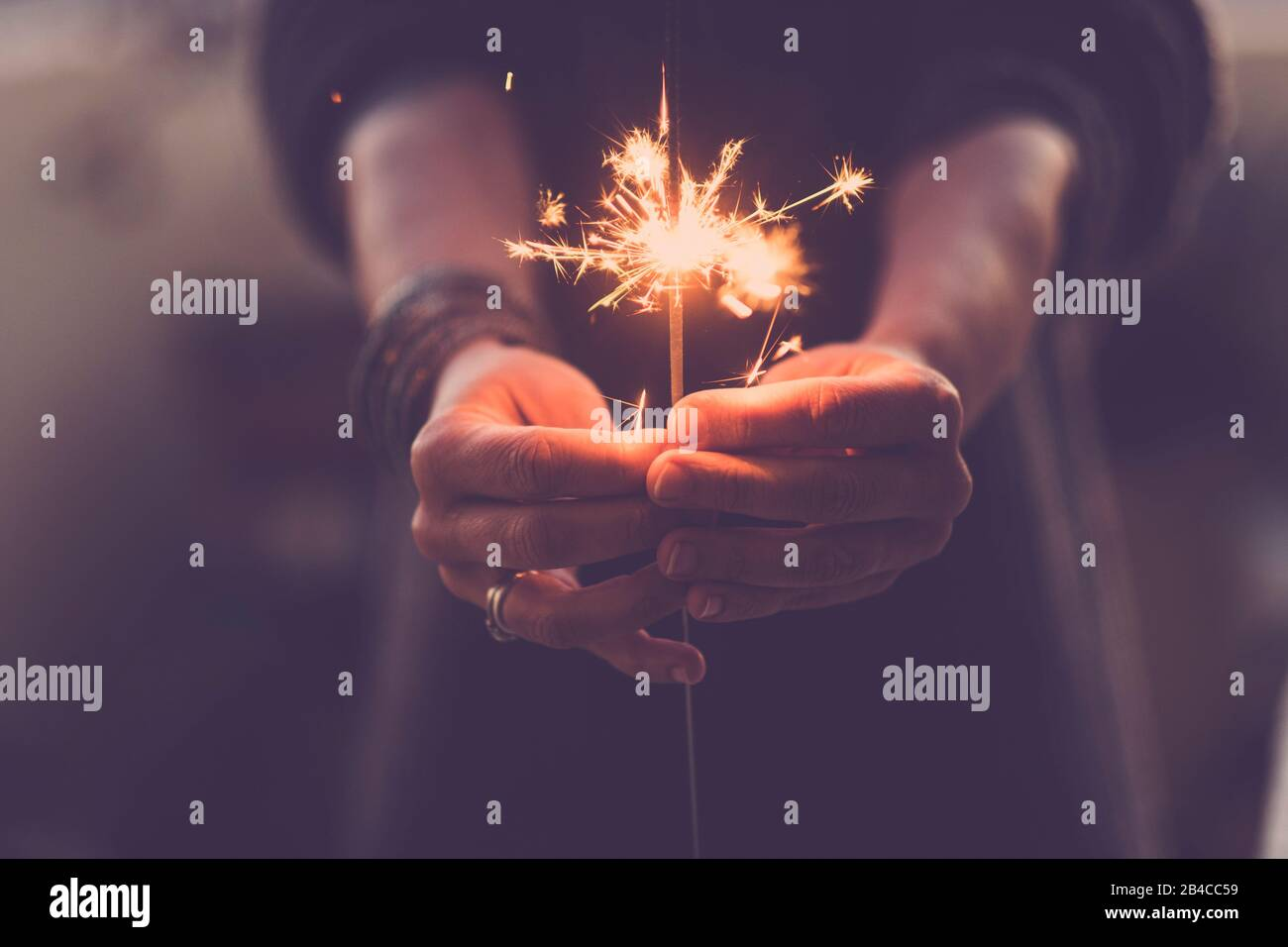 Concept of party nightlife and new year eve 2020 - close up of people hands with red fire sparklers to celebrate the night and the new start - warm colors filter Stock Photo