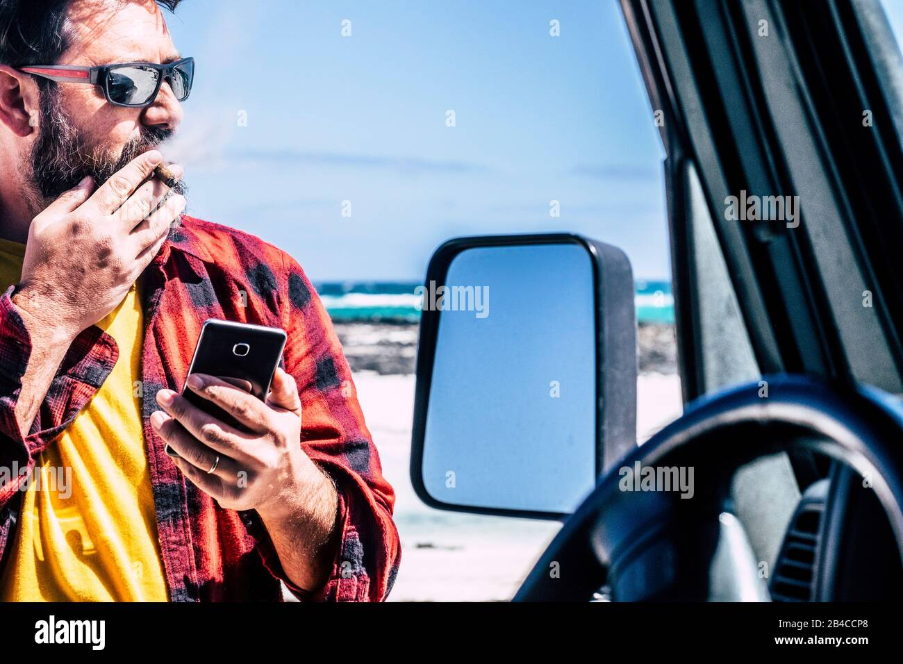Handsome standing man with cigar use mobile   phone outside his black car - beach and ocean in background for travel and adventure lifestyle concept -  people in outdoor leisure activity Stock Photo
