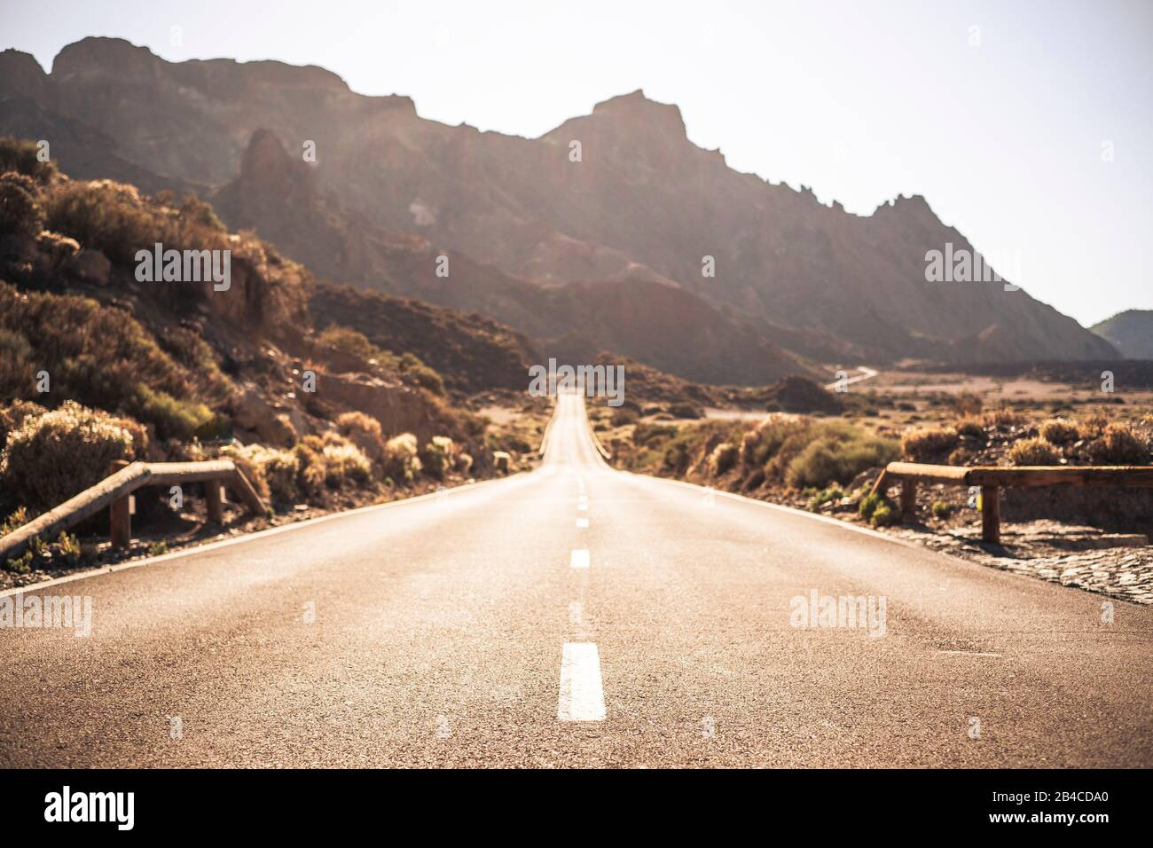 Beautiful and scenic long way road with focus on foreground - defocused background and travel destination effect with sunilght and mountains Stock Photo