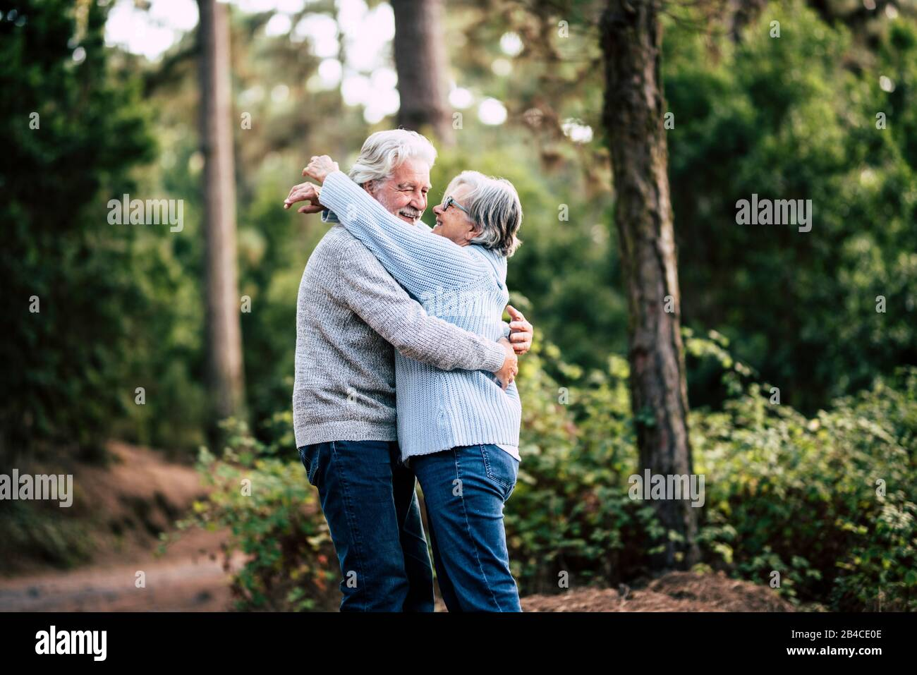 Senior active couple enjoying the outdoor nature forest with hugs and love together - forever life concept with mature man and woman - elderly and beautiful forest green in background Stock Photo