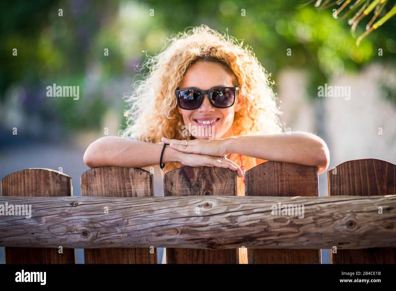 Portrait of beautiful cheerful happy woman with sun in backlight and nice smile looking at the camera - green nature background - enjoying the outdoor leisure activity in the countryside Stock Photo