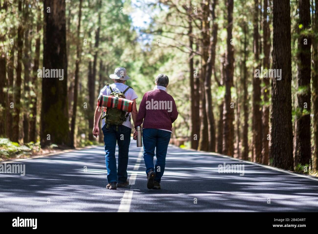 Travel lifestyle for old senior couple walking together in the middle of the road with high trees forest on both sides - lifestyle and togetherness forever life concept - aged people Stock Photo