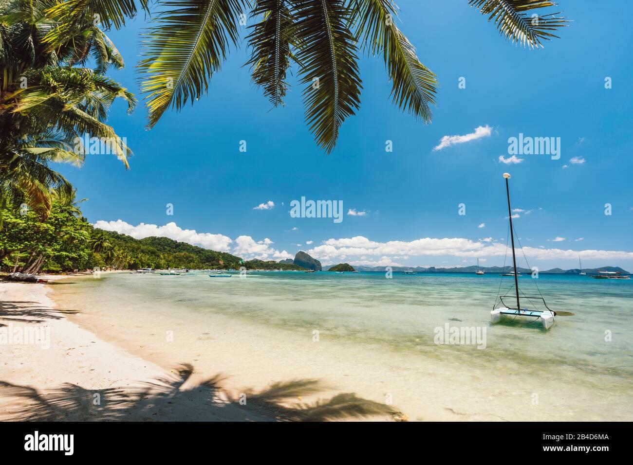 Beautiful exotic travel background, Tropical blue ocean lagoon with catamaran boat , Corong beach, El Nido, Philippines, Stock Photo