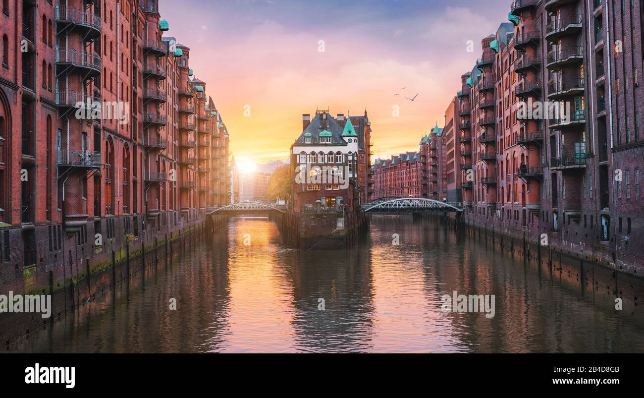 Old port of Hamburg, Germany, Europe, historic warehouse district with moated palace in the golden light of sunset Stock Photo