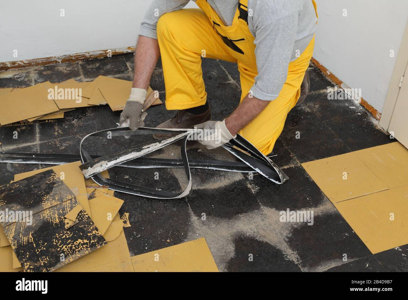 Worker Removing Old Vinyl Tiles And Batten From Kitchen Floor