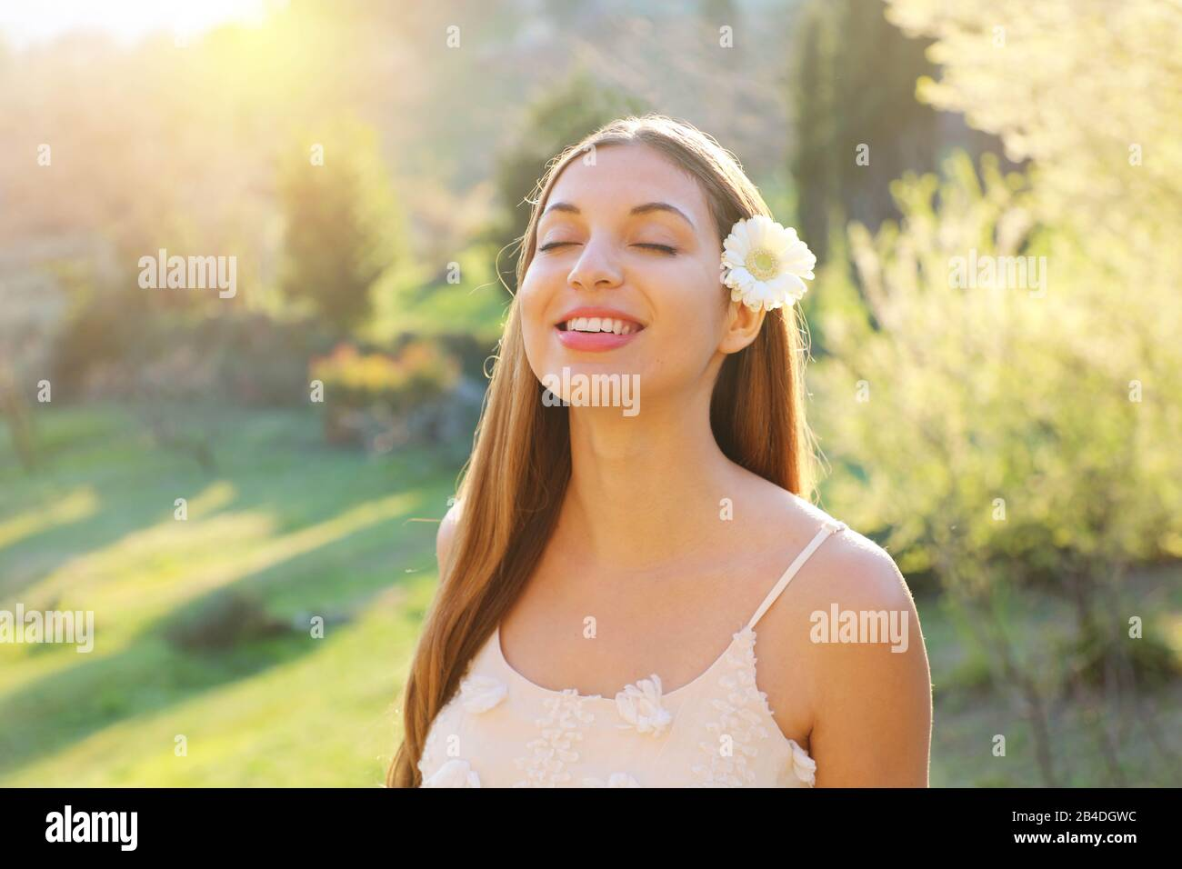 Pretty beautiful girl with closed eyes and flower on ear smiling enjoying breathing fresh air outdoor Stock Photo
