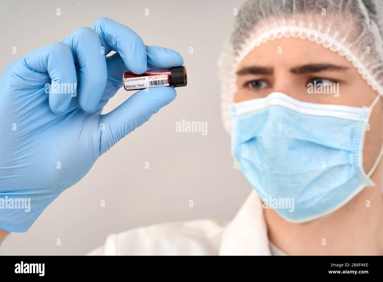 Coronavirus concept. Doctor in protective coverall and face mask holding blood sample in hand, checking test results and standing against grey backgro Stock Photo