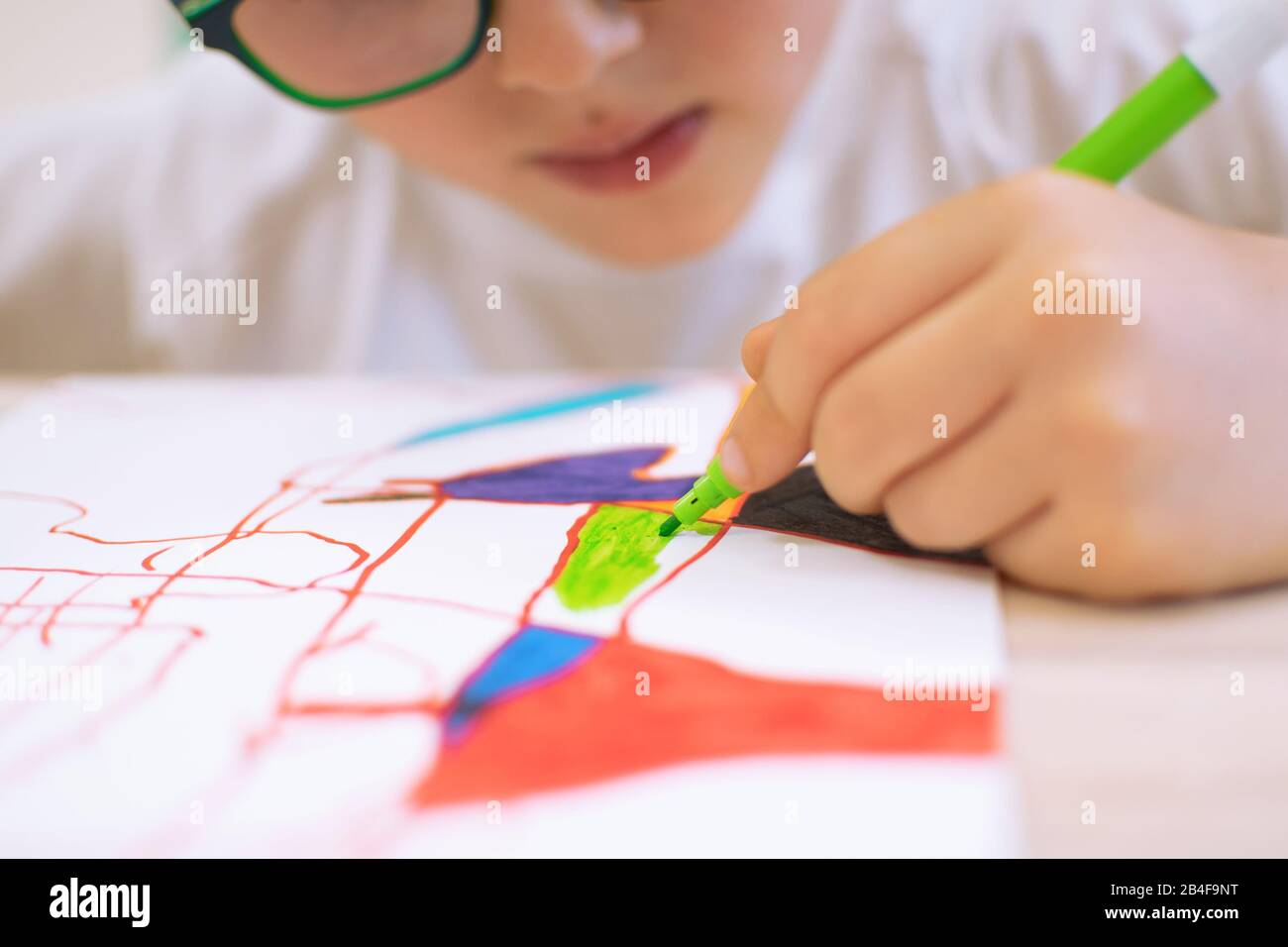 Child drawing abstract forms on a paper on vibrant colours. Introducing abstract form through the shadow of objects in art education class at school Stock Photo