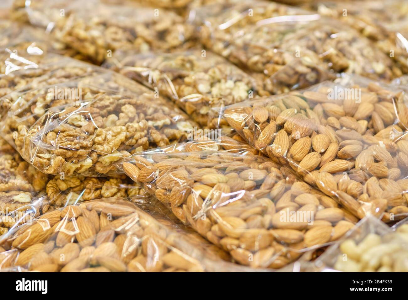 Packaging from a transparent bag with almonds and walnuts. Close up. Stock Photo