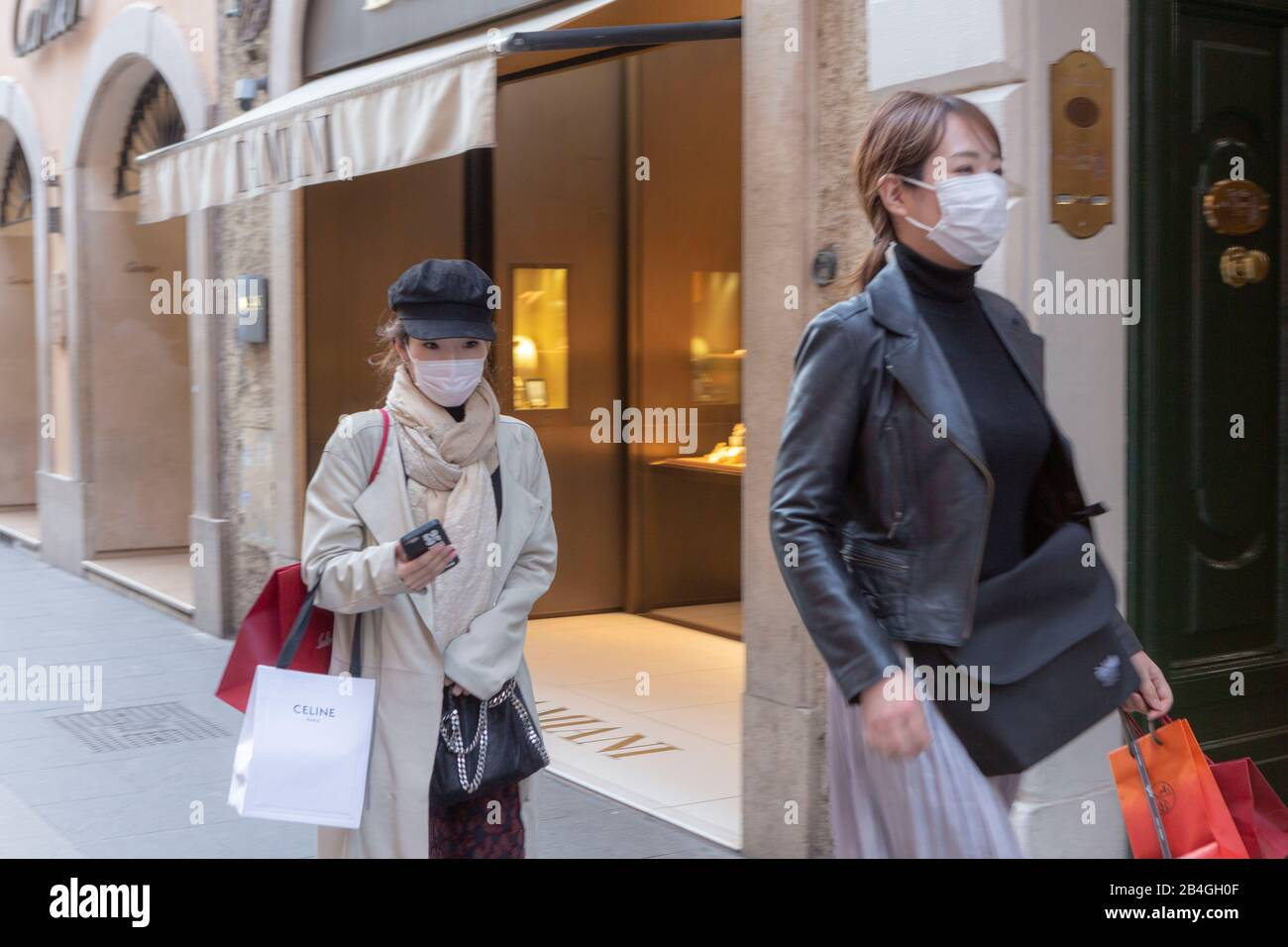 Two young Oriental women wearing surgical face masks against flu in the fashionable Via Condotti in Rome Stock Photo
