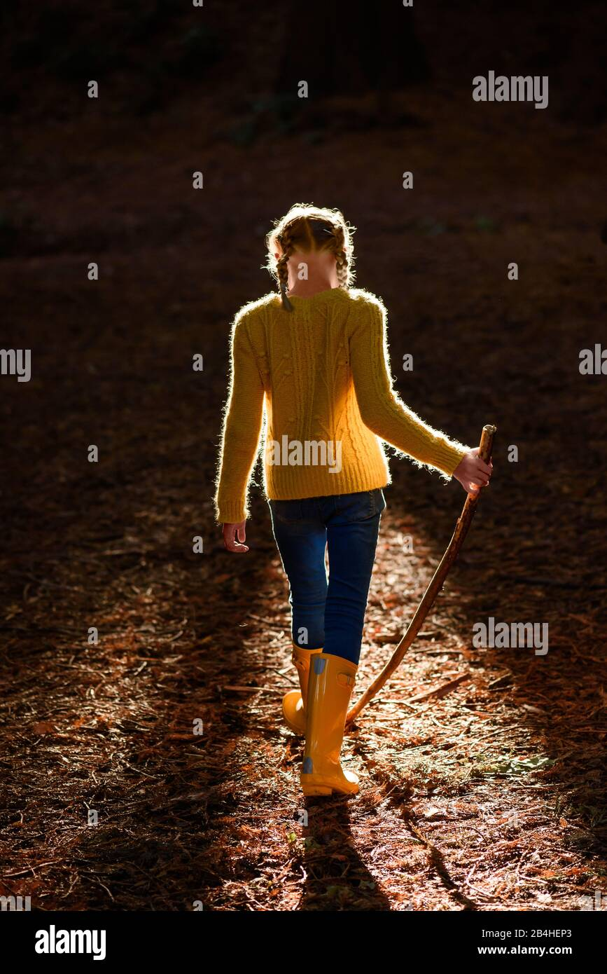 Tween girl with walking stick in forest with beautiful light Stock Photo