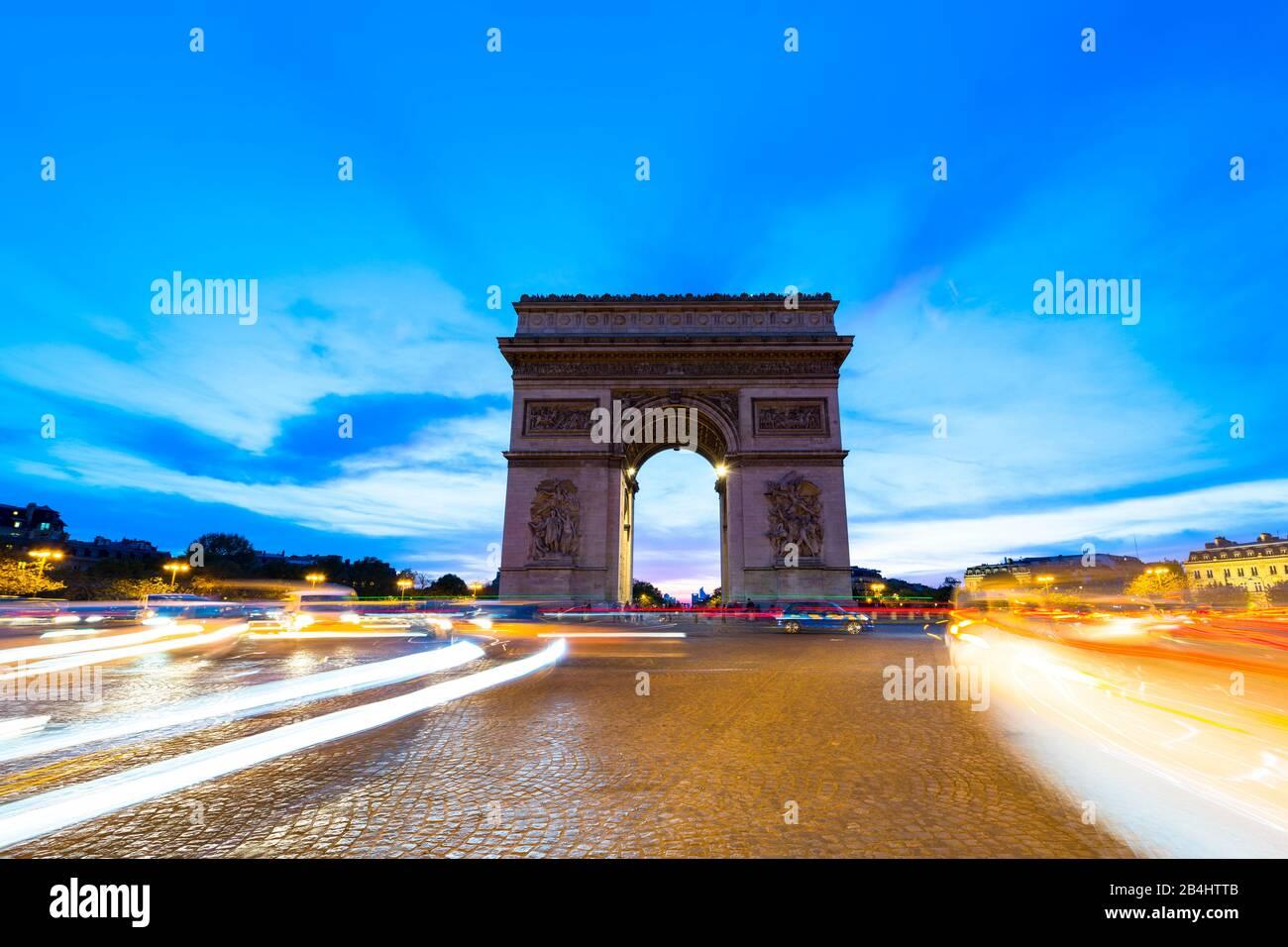fahrende Autos auf der Place Charles de Gaulle und der Triumpfbogen bei Abenddämmerung, Paris, Frankreich, Europa Stock Photo