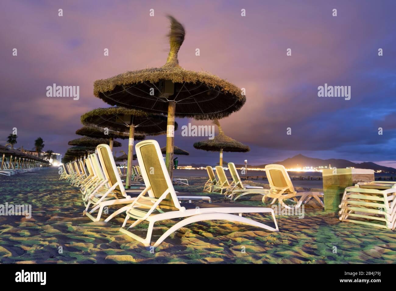 Spain, Mallorca, Playa de Muro, umbrellas and sun loungers on the beach Playa de Muro at the blue hour, north of Majorca. Stock Photo