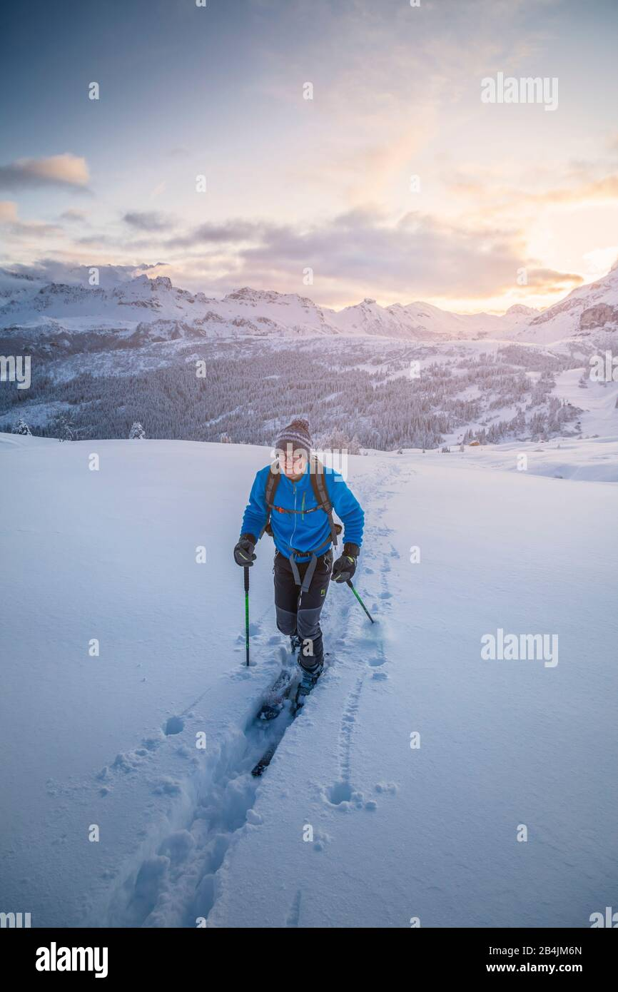 20 years young ski mountaineer follows a trail in fresh snow at sunset, Pralongia plateau, Corvara in Badia, Badia valley, South Tyrol, Italy, Europe Stock Photo