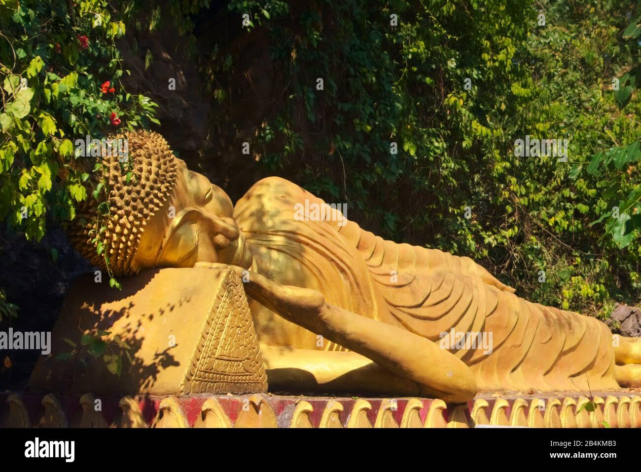Golden statue of reclining Buddha on the way to the top of Mount Phou Si, a sacred mountain in Luang Prabang, Laos. Stock Photo