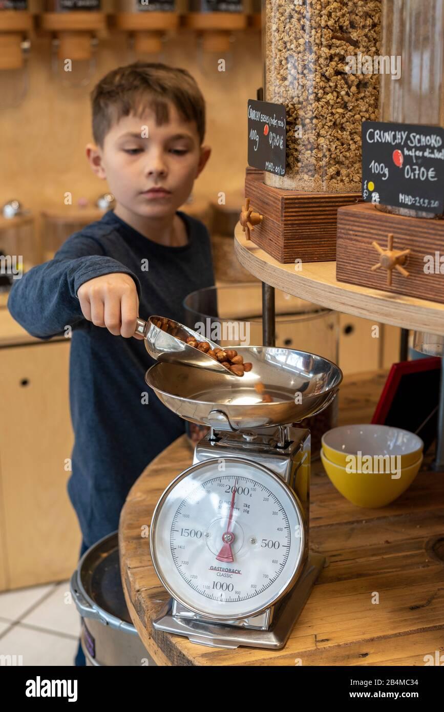 Eine Junge steht in einem Unverpacktladen an einem Regal mit Abfüllbehältern für Cerealien. Er wiegt Haselnüsse ab. Stock Photo