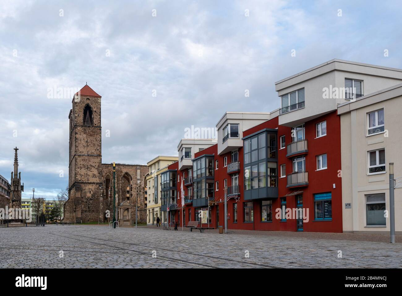 Germany, Saxony-Anhalt, Zerbst, view of modern residential buildings with the tourist information of Zerbst. In the background you can see the ruins of the St. Nikolai town church. They were destroyed in the last days of the war in 1945. Stock Photo