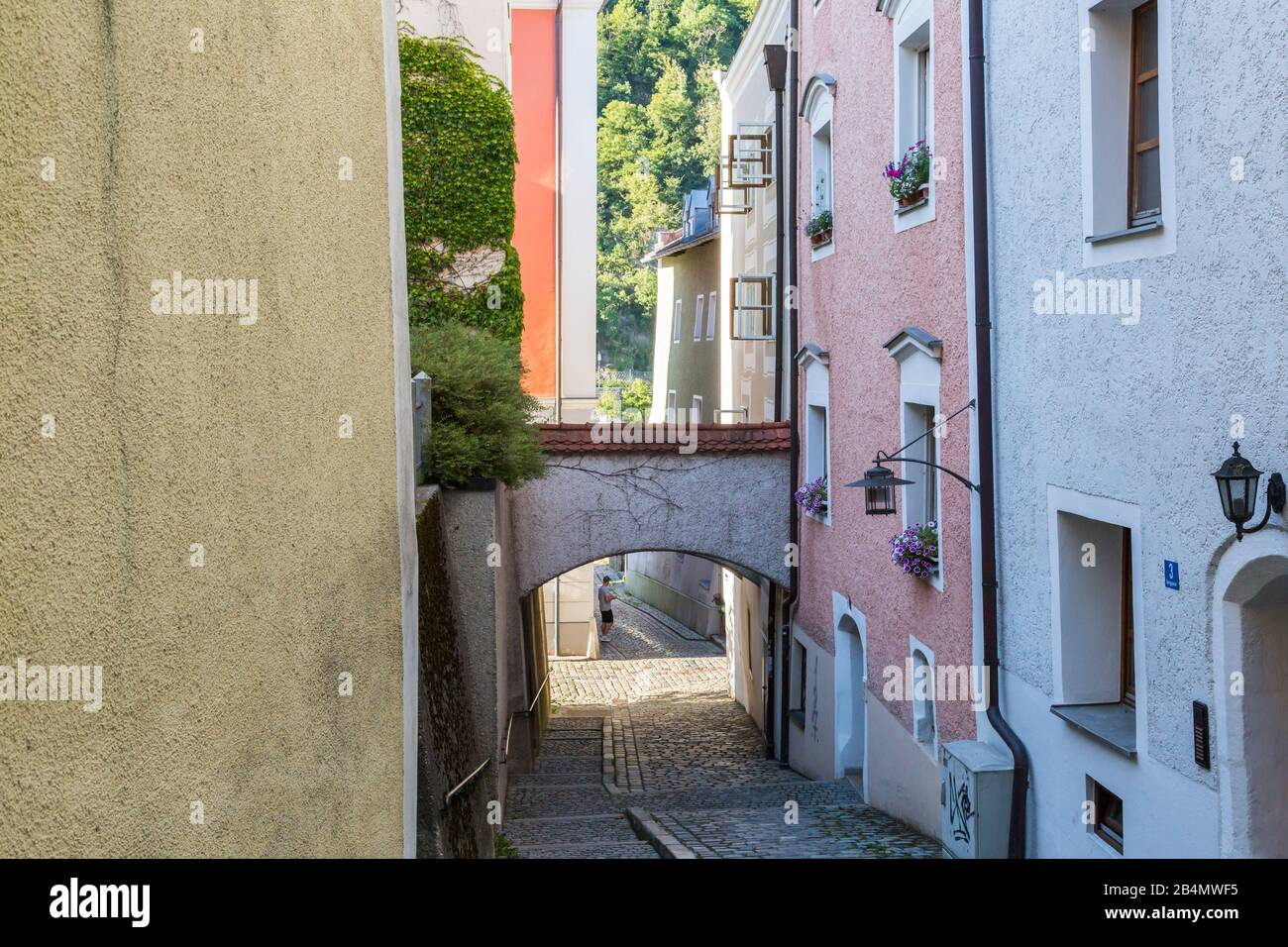 Quaint narrow cobbled lane in Passau, Bavaria, Germany in summer with arch between the buildings and view to trees Stock Photo