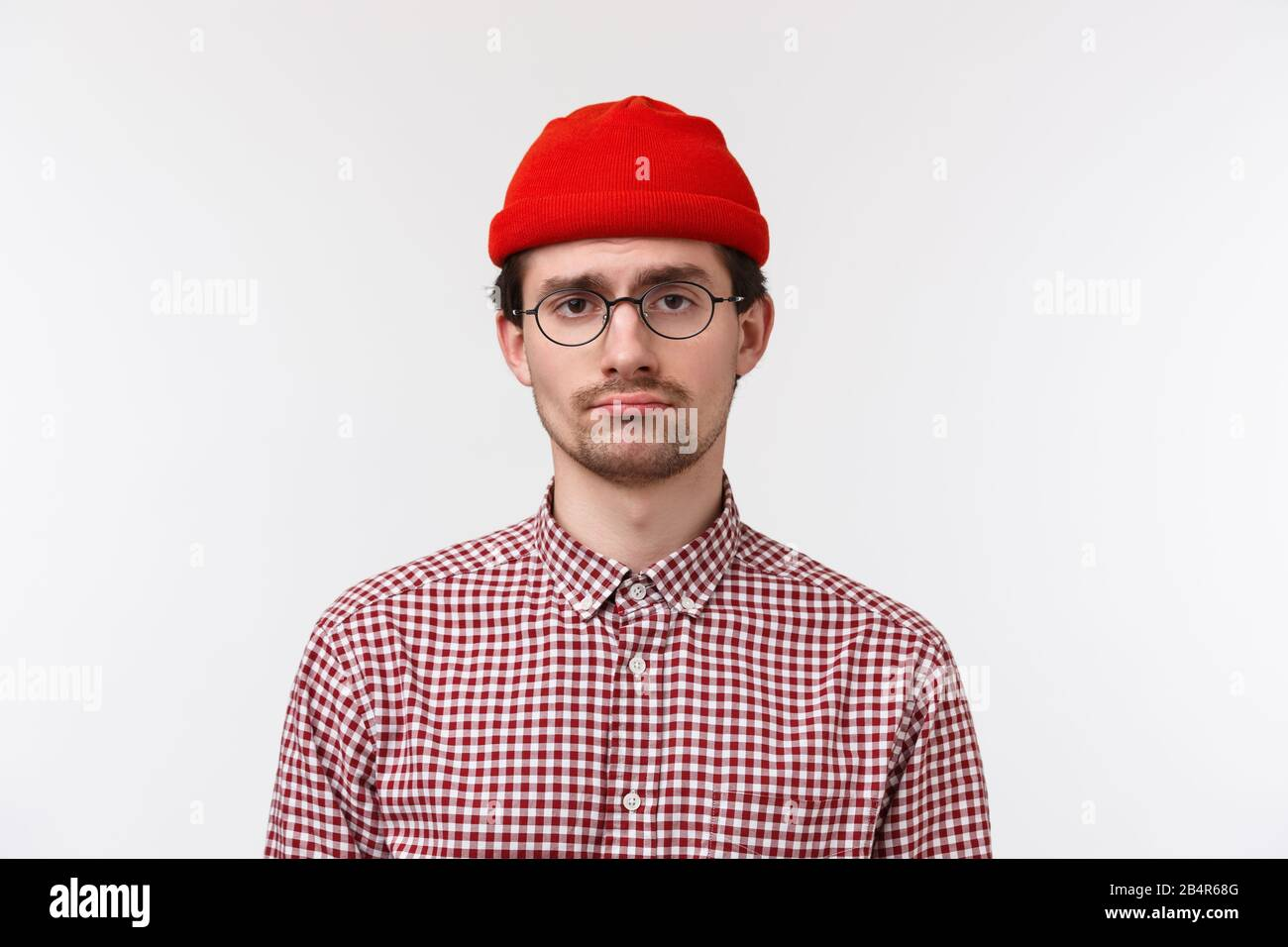 Close-up portrait of bored and reluctant young hipster guy feeling like  loser, having bad unlucky day, standing in glasses and red beanie, feel  lonely Stock Photo - Alamy