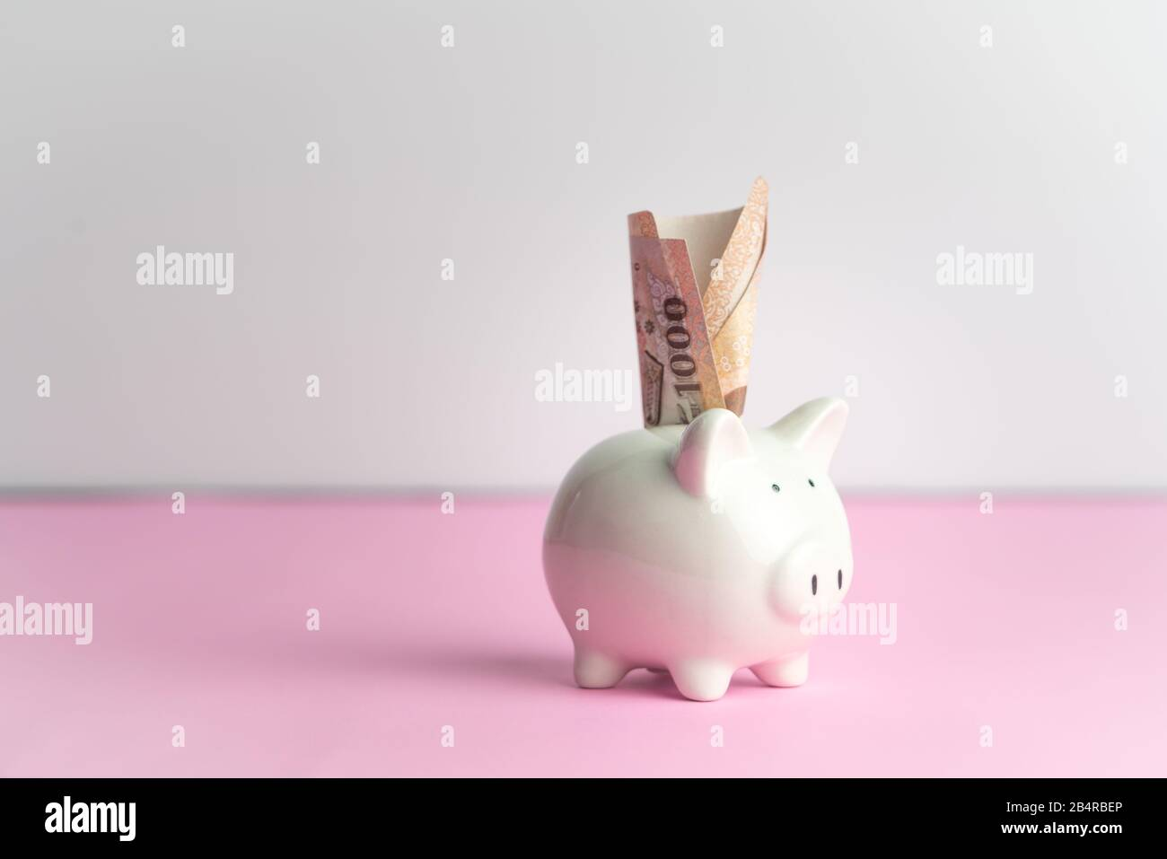 Money saving and donation concept, money on cute white piggy bank on pink table Stock Photo