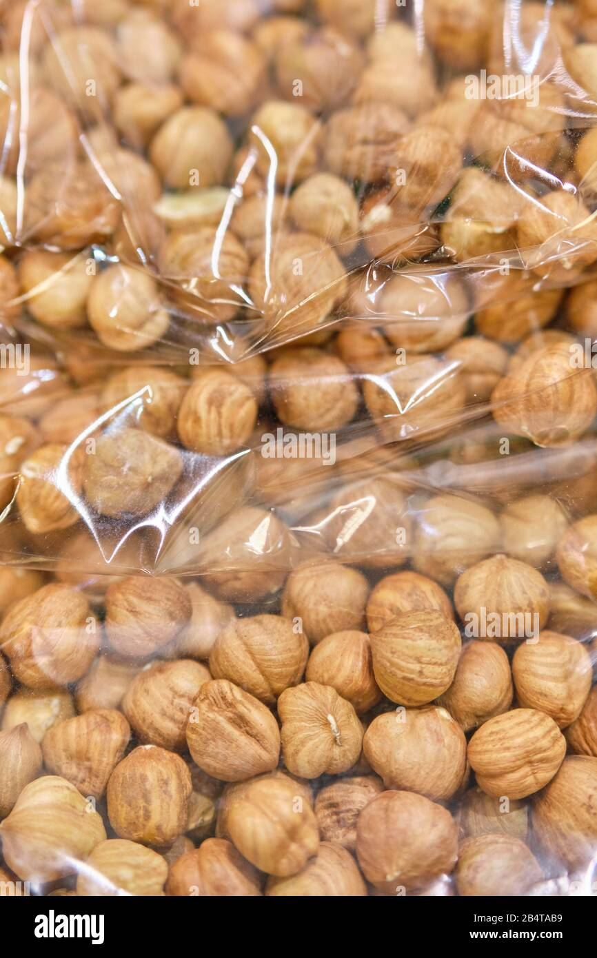 Packing from a transparent bag with peeled hazelnuts. Close up. Vertical. Stock Photo