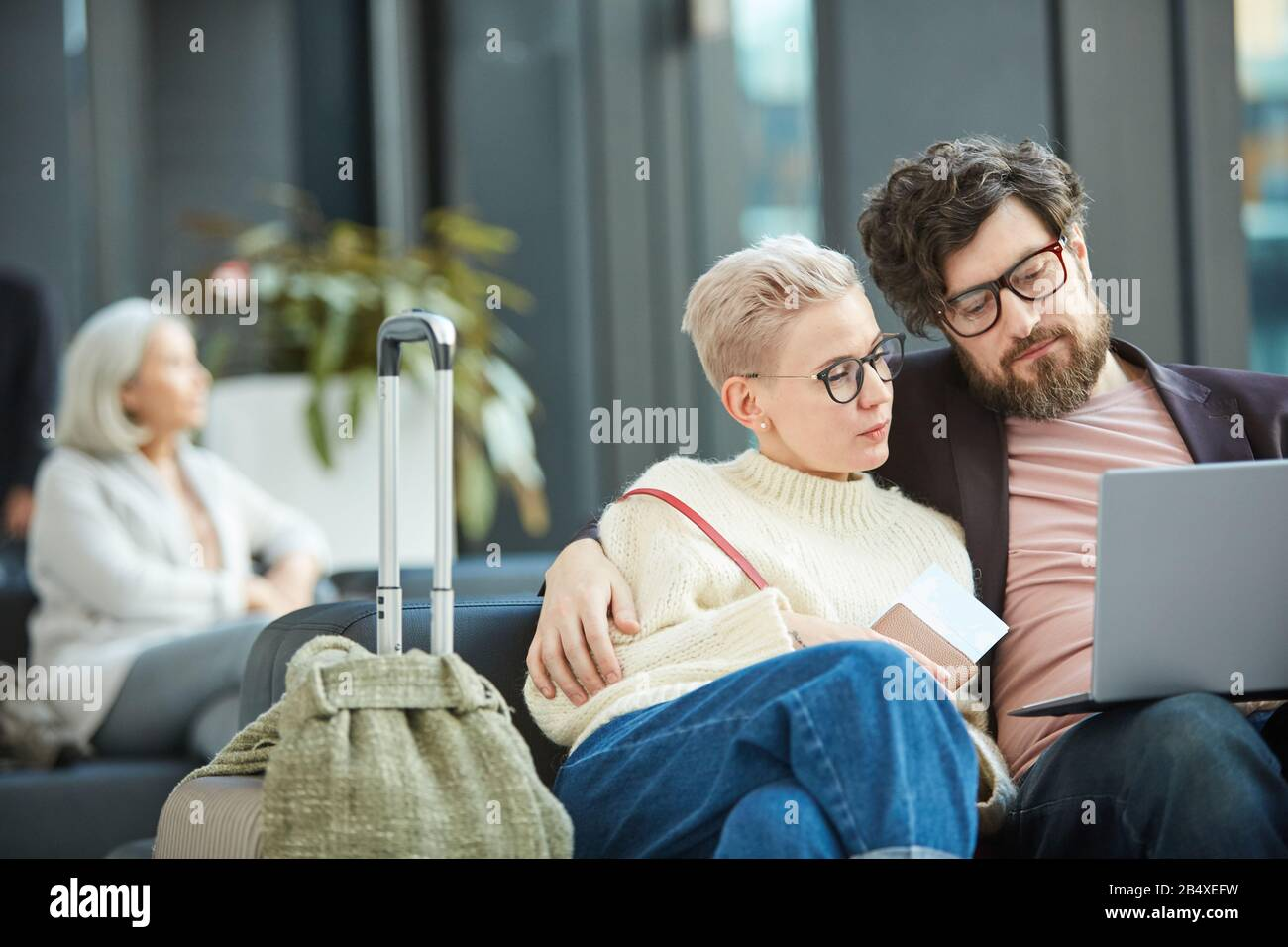 Young Man And Woman In Love Sitting Together In Departure Lounge Waiting For Flight Watching Something On Their Laptop Copy Space Stock Photo Alamy