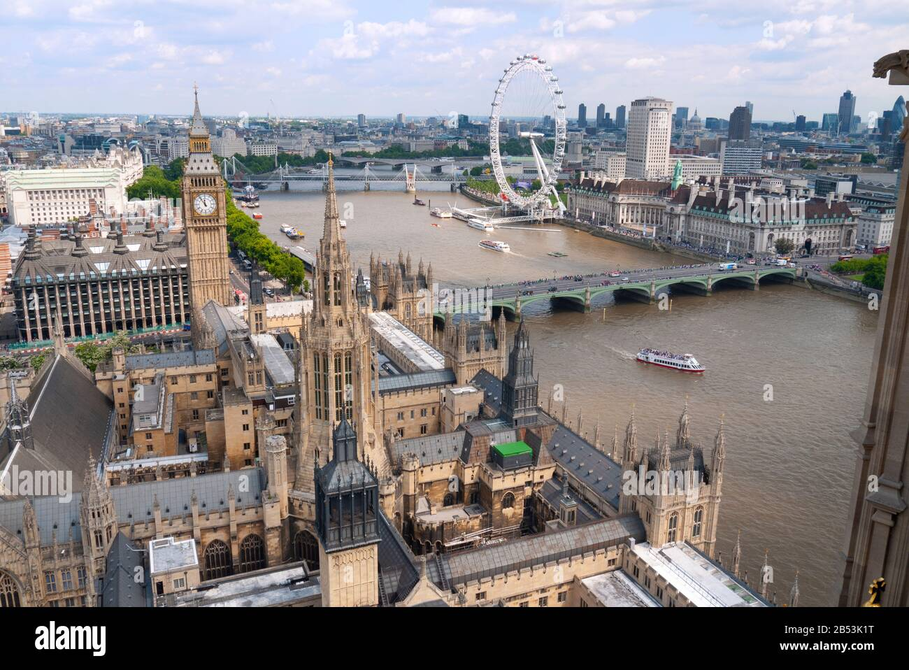 View looking over Palace of Westminster along River Thames towards the London Eye showing St Stephen's and Elizabeth towers. London, United Kingdom Stock Photo