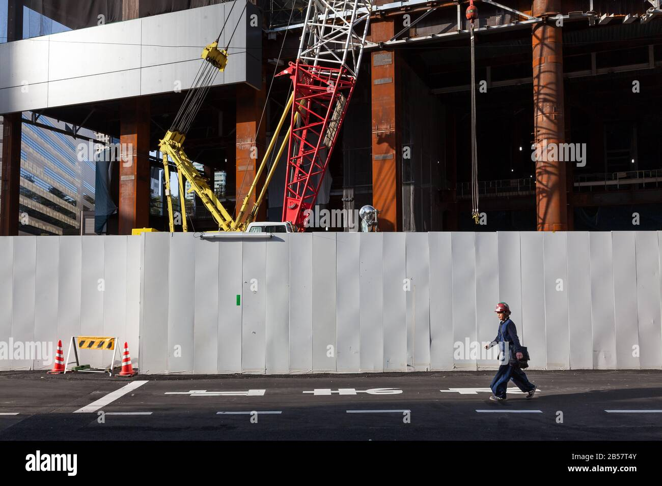 A construction worker walks past the wall of a construction site early in the morning. Akasaka, Tokyo, Japan. Friday April 15th 2016 Stock Photo