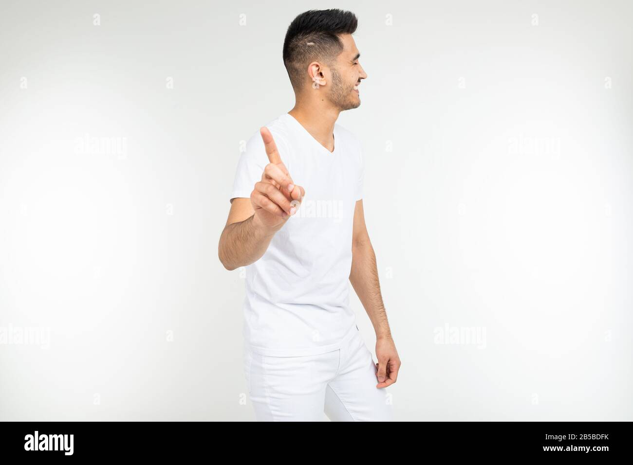 smiling man points his finger at the viewer and warns against a white studio background Stock Photo