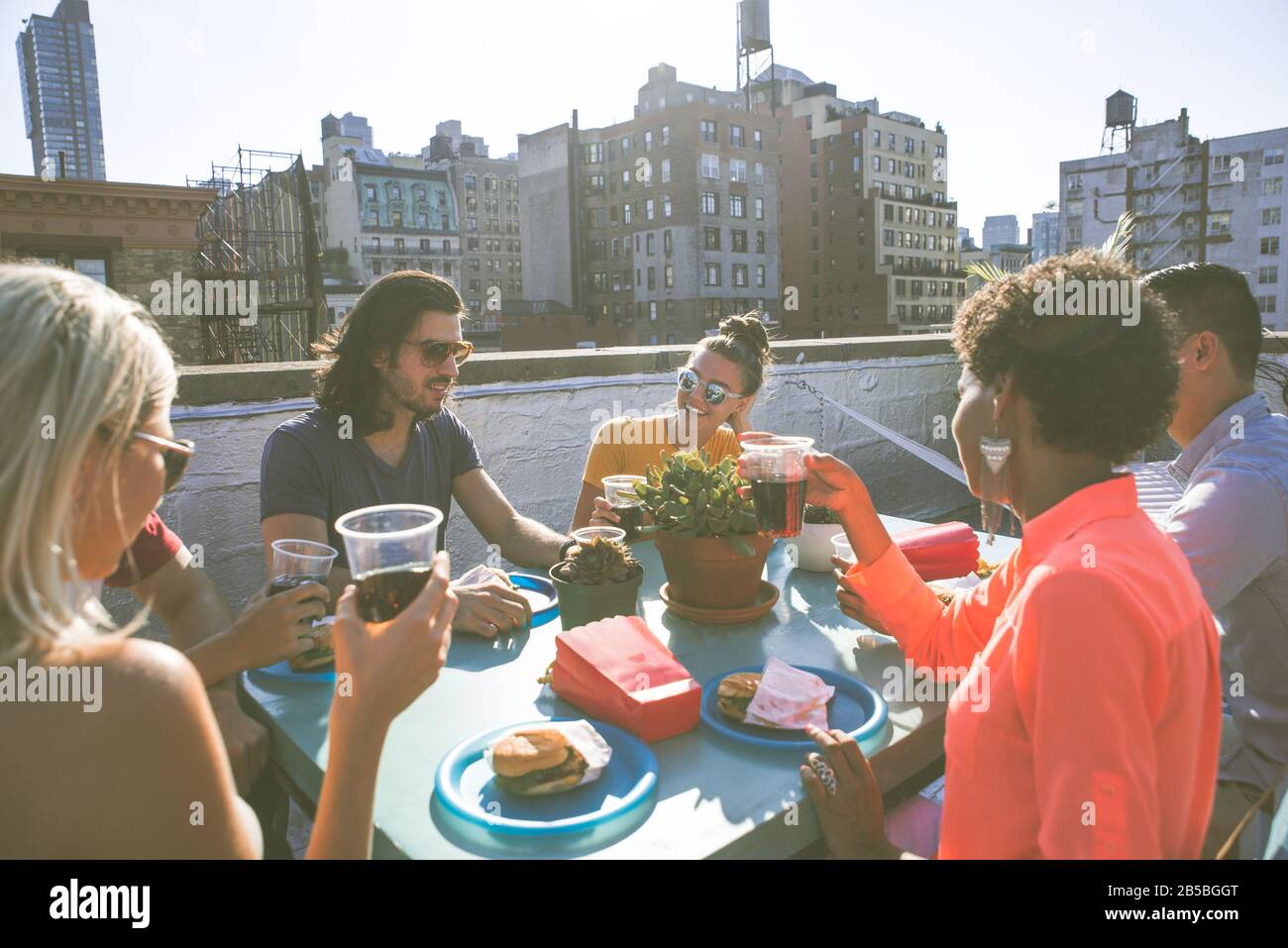Group of friends apending time together on a rooftop in New york city, lifestyle concept with happy people Stock Photo