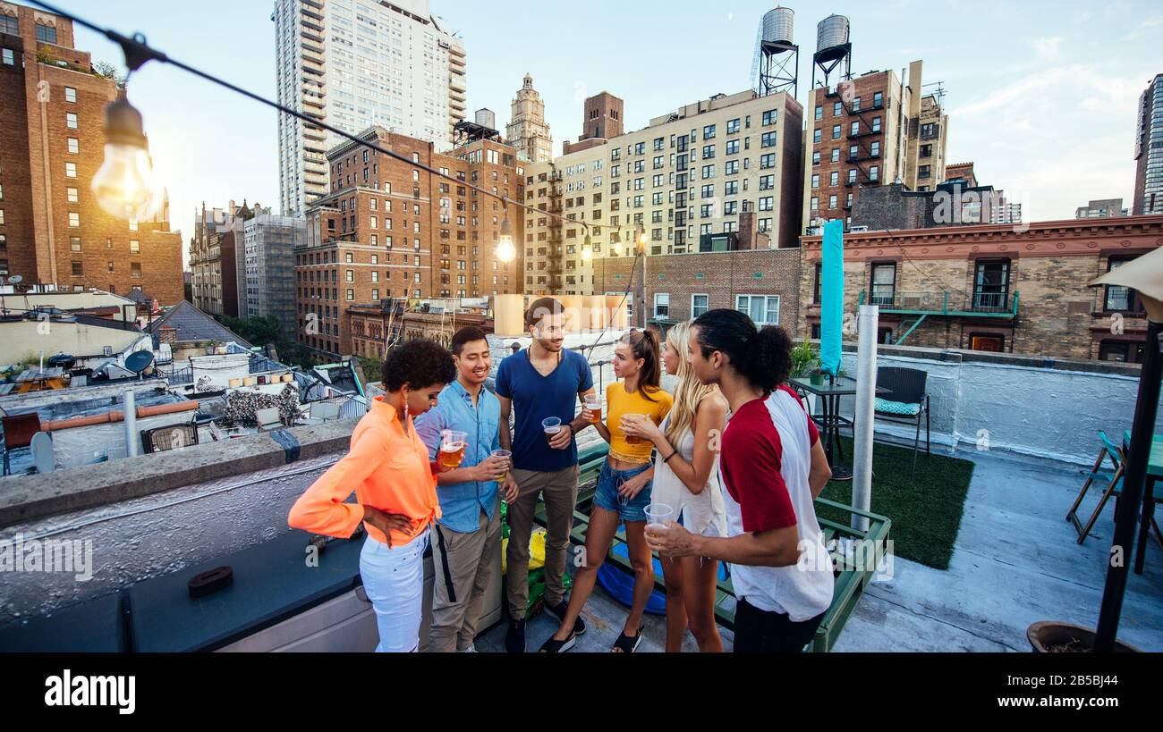 Group of friends spending time together on a rooftop in New york city, lifestyle concept with happy people Stock Photo
