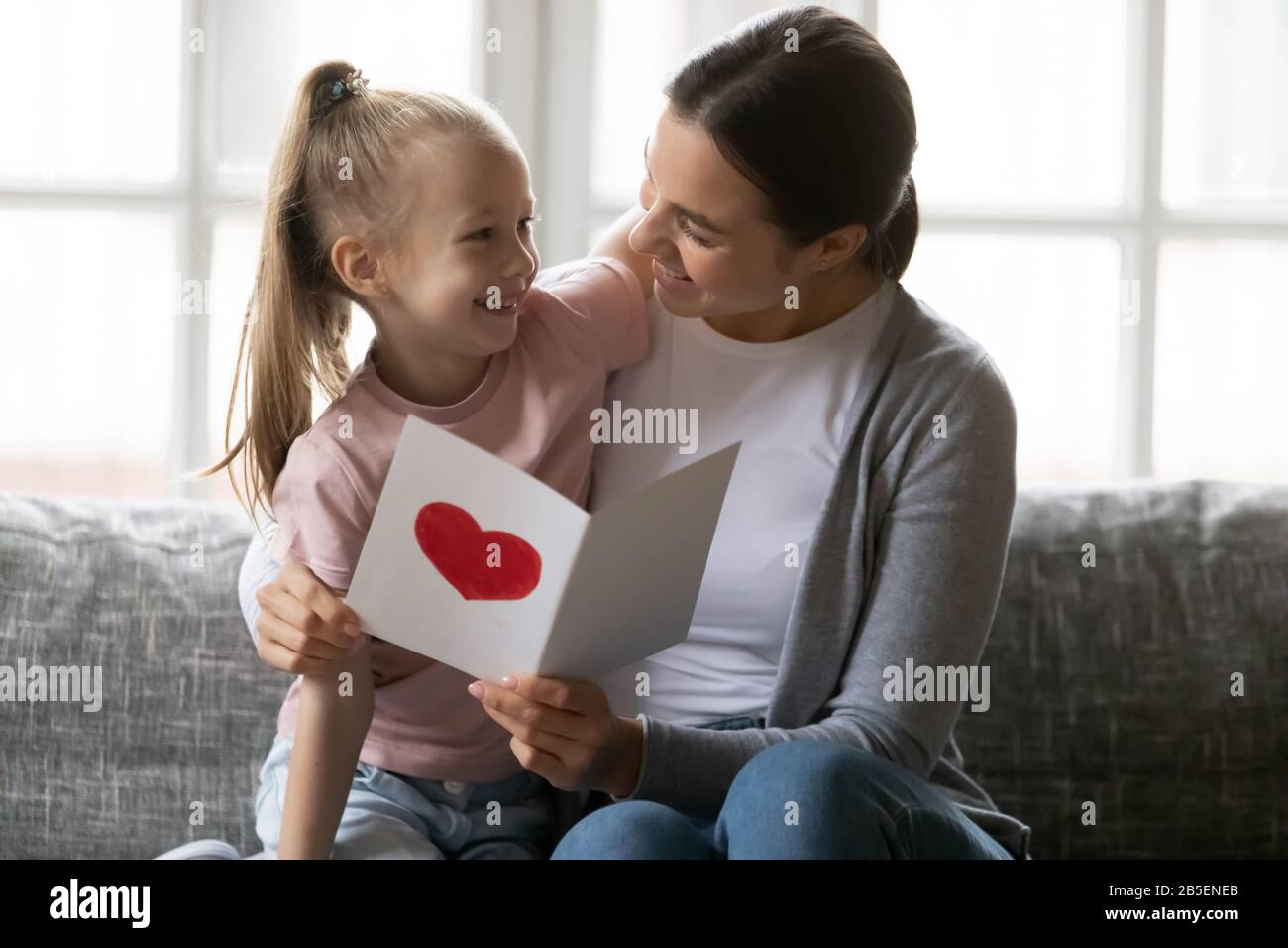 Affectionate Loving Mother Embracing Little Daughter Reading Congratulations In Card Stock Photo Alamy