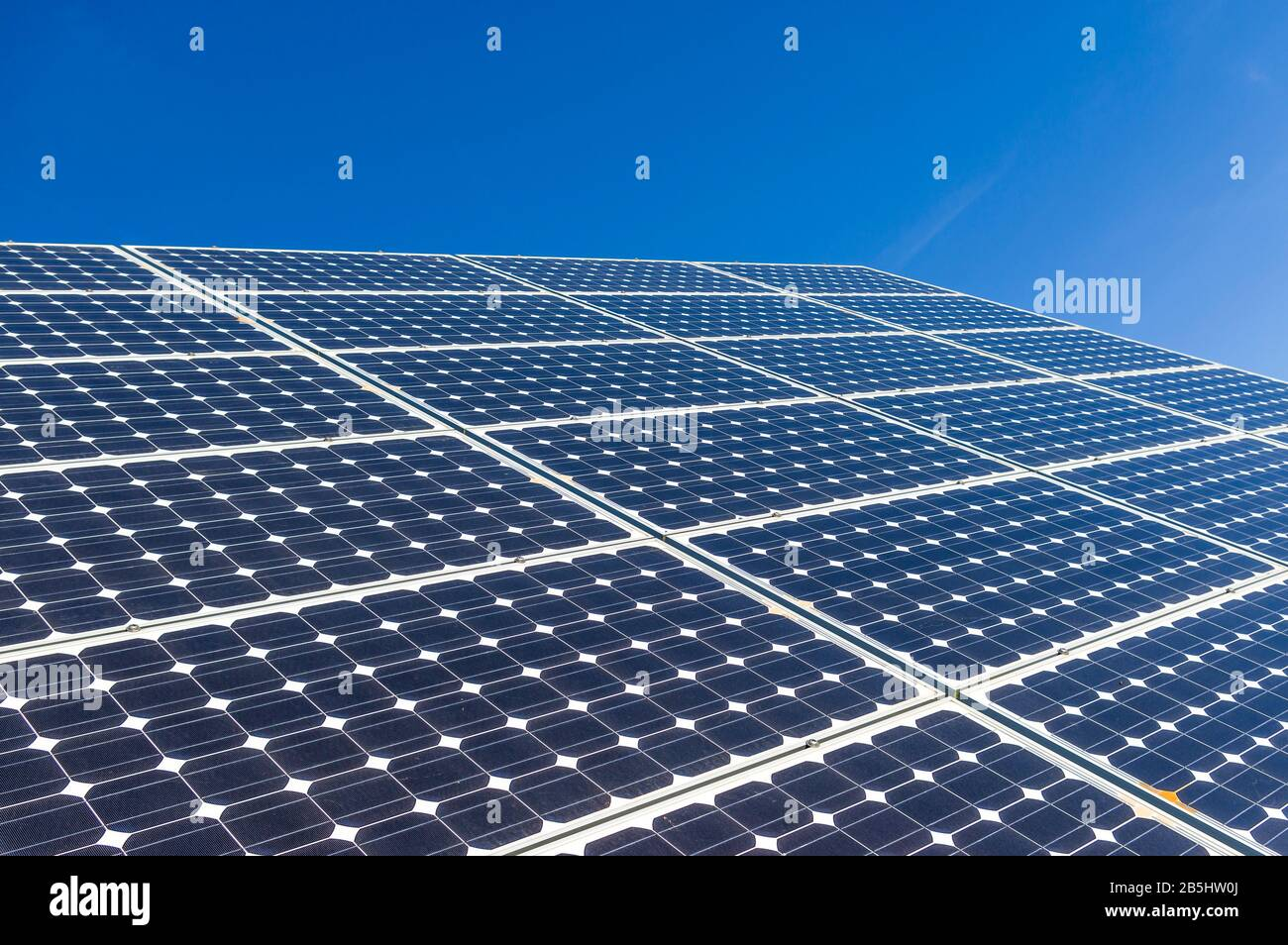 Close-up, detail view of solar panels of a solar power plant in cloudless and bright blue sky Stock Photo
