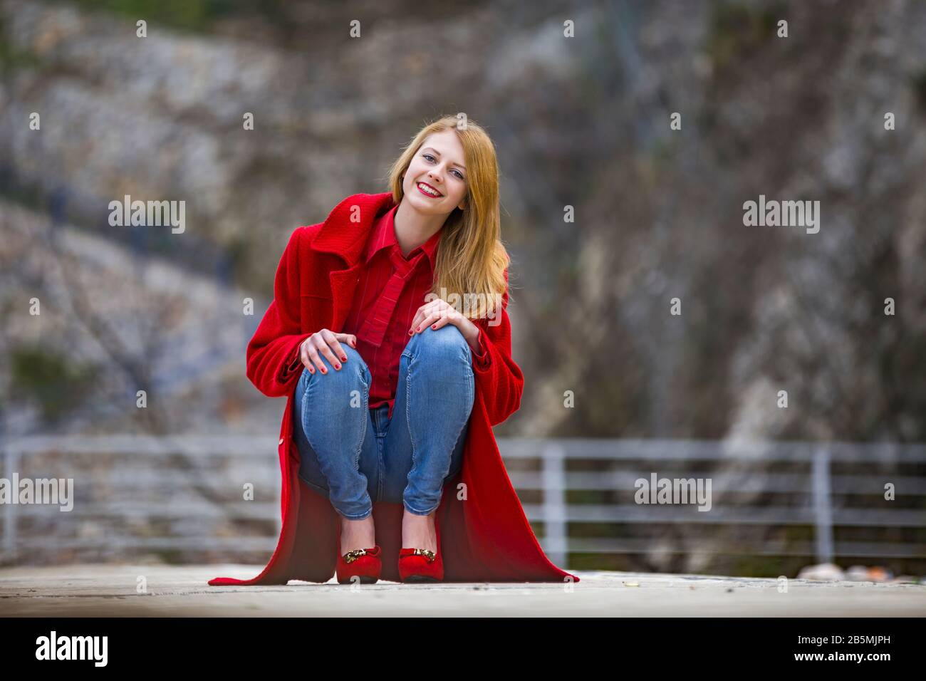Teenager girl is smiling at camera eyeshot eye-eyes contact isolated from background squatting wearing Blue-denim pants Red coat and pumps highheels Stock Photo