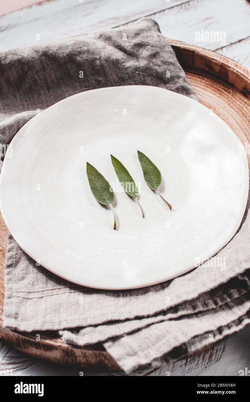 Minimalistic stock photo of sage leaves on white plate stock photo Stock Photo