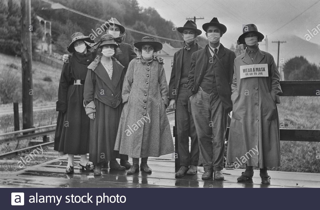 """A group of people standing outdoors wearing masks over their mouths. This was probably during the Spanish Flu epidemic of 1918. One of the women has a sign in front of her reading 'Wear a mask or go to jail."""" Stock Photo"""