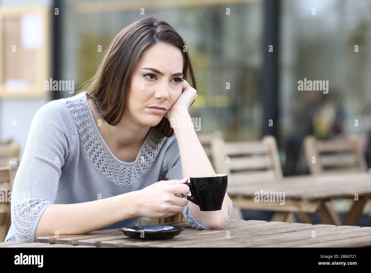 Sad young woman looking away holding a cup of coffee on a restaurant terrace Stock Photo