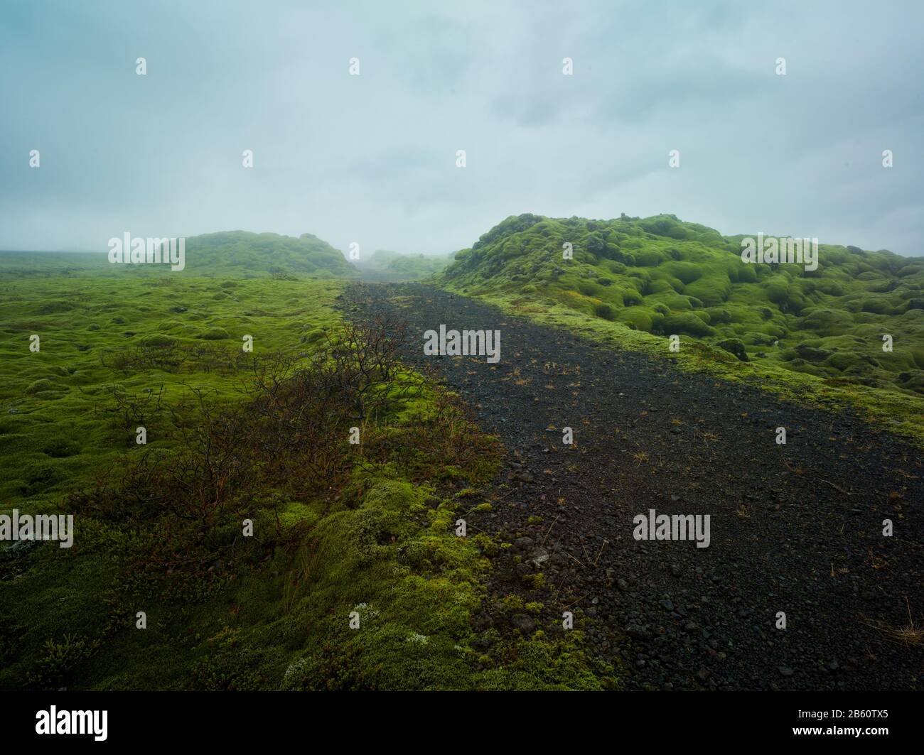 Gravel road leading into a misty valley, rocky mossy green landscape volcanic dirt track moor lands Stock Photo