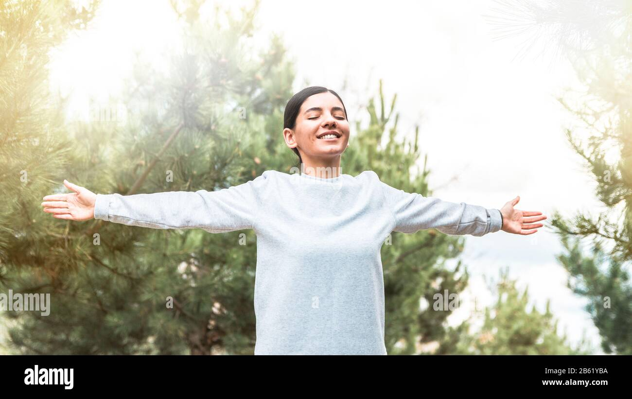 soul and body freedom. attractive woman with arms open and eyes closed meditating and understanding her being in nature at sunrise Stock Photo