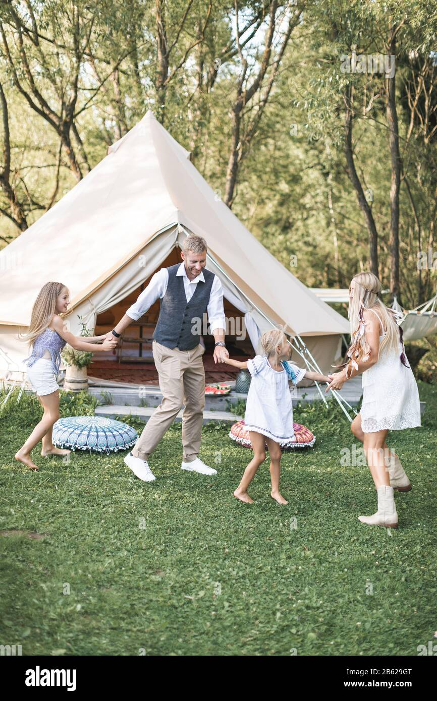 Young stylish family with children have fun in a park. Father, mother and daughters dancing in nature together, holding hands. Family dancing near Stock Photo